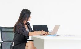 Donna che utilizza computer portatile nell'ufficio isolato su bianco immagine stock