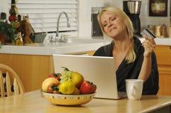 Donna che utilizza computer portatile nella cucina Fotografie Stock Libere da Diritti