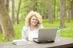 Donna che utilizza computer portatile nella sosta Fotografie Stock Libere da Diritti