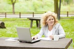 Donna che utilizza computer portatile nella sosta Fotografia Stock
