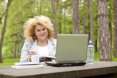 Donna che utilizza computer portatile nella sosta sulla tabella di legno Fotografia Stock
