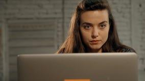 Donna che utilizza funzionamento del computer portatile del pc sul nuovo progetto nella società video d archivio