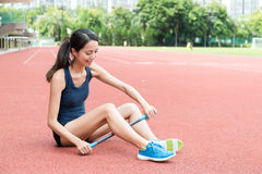 Donna che utilizza il bastone di massaggio del rullo nello stadio di sport Fotografia Stock Libera da Diritti