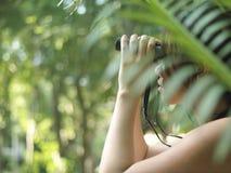 Donna che utilizza il binocolo nella foresta Immagine Stock