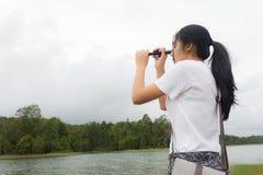 Donna che utilizza il binocolo nella foresta attuale Immagini Stock