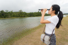 Donna che utilizza il binocolo nella foresta attuale Fotografia Stock Libera da Diritti