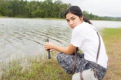 Donna che utilizza il binocolo nella foresta attuale Fotografia Stock