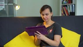 Donna che utilizza il PC della compressa nel suo Appartement video d archivio