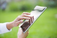 Donna che utilizza il pc digitale della compressa nel parco. immagini stock libere da diritti