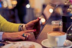 Donna che utilizza la compressa di Digital nel caffè fotografie stock libere da diritti