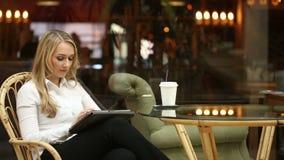 Donna che utilizza lo schermo attivabile al tatto del computer della compressa nel caffè bevente del caffè stock footage