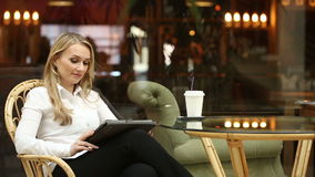 Donna che utilizza lo schermo attivabile al tatto del computer della compressa nel caffè bevente del caffè video d archivio