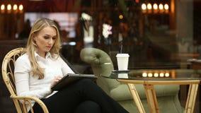 Donna che utilizza lo schermo attivabile al tatto del computer della compressa nel caffè bevente del caffè archivi video