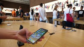 Donna che utilizza nel deposito di Apple l'ultimo nuovo smartphone 10 di iPhone X di Apple stock footage