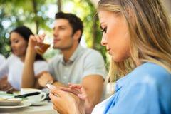 Donna che utilizza smartphone mentre sedendosi nel ristorante all'aperto Fotografia Stock Libera da Diritti