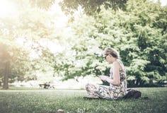 Donna che utilizza smartphone nel parco pubblico fotografie stock libere da diritti