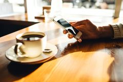 Donna che utilizza smartphone sulla tavola di legno nel caff? immagine stock