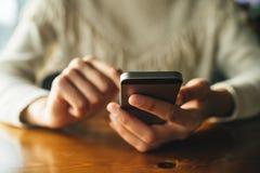 Donna che utilizza smartphone sulla tavola di legno nel caff? immagine stock libera da diritti