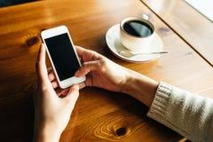 Donna che utilizza smartphone sulla tavola di legno nel caff? fotografia stock