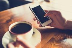 Donna che utilizza smartphone sulla tavola di legno nel caff? immagini stock libere da diritti
