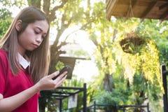 Donna che utilizza telefono cellulare mentre supporto nel parco immagini stock libere da diritti