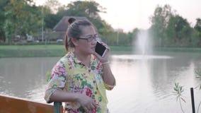 Donna che utilizza telefono cellulare nel parco pubblico