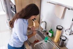 Donna che utilizza tuffatore nel lavandino di cucina bloccato immagini stock libere da diritti