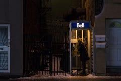 Donna che utilizza un telefono a gettone di Bell Canada a Montreal nella sera sotto la forte nevicata Fotografia Stock Libera da Diritti