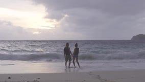 Donna che va al suo marito, essi che guardano il tramonto e che abbracciano vicino all'oceano stock footage