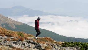 Donna che va scolarsi minimo attraverso una valle di pietra in montagna stock footage