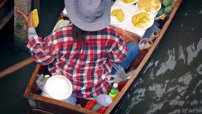 Donna che vende alimento dalla barca nel mercato del fiume video d archivio