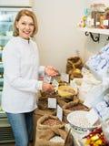 Donna che vende i fagioli in negozio Immagini Stock