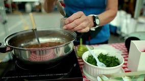 Donna che vende le minestre già pronte con un vassoio dell'assaggio al mercato dell'agricoltore stock footage