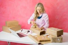 Donna che vende mercanzie online e che imballa gli oggetti per la posta fotografia stock