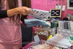 Donna che vende tessuto in deposito con le pile di tessuti variopinti fotografie stock libere da diritti