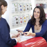 Donna che vende un telefono delle cellule fotografia stock libera da diritti