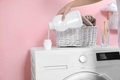Donna che versa detersivo liquido nel cappuccio sulla lavatrice nella stanza di lavanderia fotografia stock libera da diritti