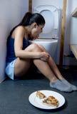 Donna che vomita e che getta su inginocchiamento sul pavimento del WC della toilette colpevole dopo il cibo della pizza fotografia stock