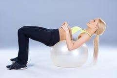Donna chiazzata che si trova sulla palla di forma fisica Fotografia Stock Libera da Diritti