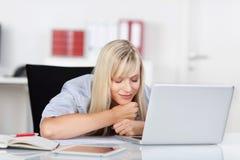 Donna chiusa degli occhi davanti al computer portatile Fotografia Stock Libera da Diritti
