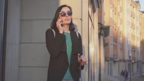 Donna cieca in vetri con una canna che parla sul telefono sulla via fotografie stock
