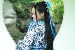 Donna cinese asiatica in vestito blu e bianco tradizionale da Hanfu, gioco in un giardino famoso, supporto davanti alla finestra immagini stock libere da diritti