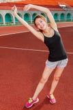 Donna cinese che allunga sulla pista allo stadio Immagini Stock