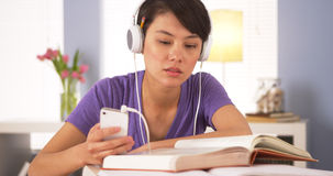 Donna cinese che ascolta la musica mentre facendo compito Fotografia Stock Libera da Diritti