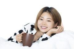 Donna cinese che pone a letto caffè bevente sul fondo bianco Immagine Stock Libera da Diritti
