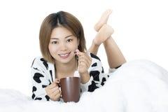 Donna cinese che pone a letto tè bevente sul fondo bianco Fotografia Stock Libera da Diritti