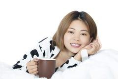 Donna cinese che pone a letto tè bevente sul fondo bianco Fotografie Stock