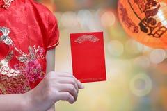 Donna cinese che tiene la busta del nuovo anno o bao rossa di hong Immagine Stock Libera da Diritti