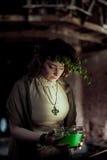 Donna in ciotola della tenuta della corona con liquido Fotografie Stock