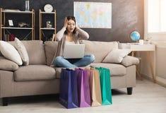 Donna colpita che compra online con il computer portatile e la carta di credito Fotografia Stock